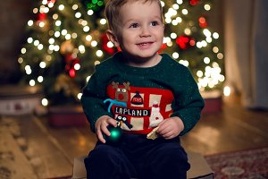 baby boy sitting near Christmas tree