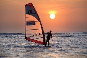 Man windsurfing at sunset