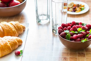 Croissants and raspberries on the table.