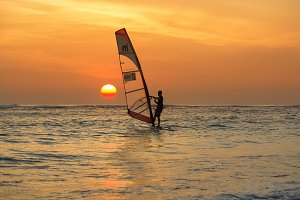 Man windsurfing at sunset
