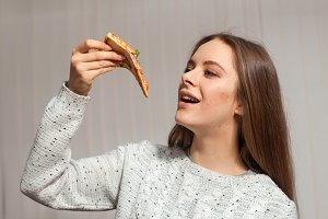 woman is keeping a slice of pizza