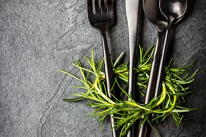 Set of cutlery and rosemary on black stone slate background.