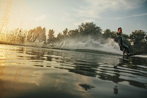 Wakeboarder skiing on lake
