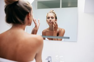 Woman in bathroom applying cream