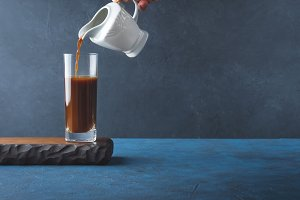 Pouring coffee in long glass on dark background