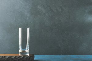Dark black background with empty glass on wooden board