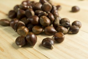 Chestnuts on pine wood background.