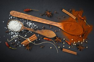 Wooden spoon with spices on a black background