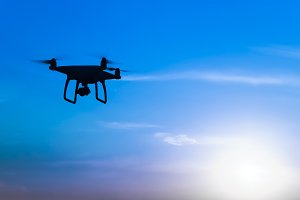 Quadrocopters silhouette against the background of the sunrise