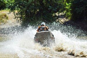 The man on the ATV crosses a stream. Tourist walks on a cross-country terrain