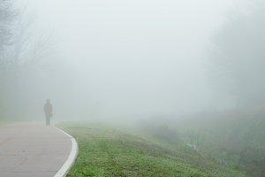 Person walking along path in fog