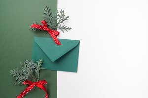 Green envelope on christmas holiday background. Flat lay.