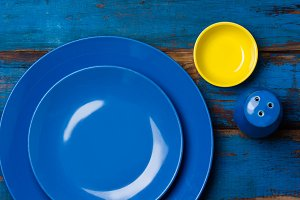 Colorful blue yellow background with empty plates