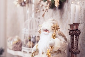 White Santa sitting on classical fireplace. Winter concept.