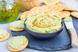 Healthy avocado hummus sprinkled with olive oil, paprika and sesame, served with crackers, horizontal