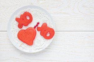 Red velvet pancakes with xo sign (hugs and kisses) and heart on white plate, horizontal, top view, copy space