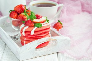 Stack of red velvet pancakes with yogurt and strawberry on on wooden tray, horizontal, copy space