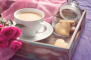 Cup of coffee, cookies and rose.