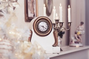 White vintage clock at the burning candles background.