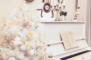 White Christmas tree with hand made ornaments and white piano. Winter time. New Year holiday.