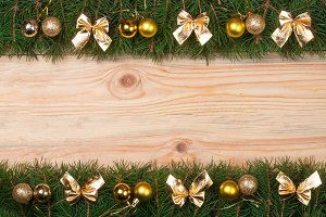 Christmas frame made of fir branches decorated with golden bows and balls on a light wooden background