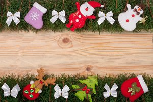 Christmas frame made of fir branches decorated with white bows Snowman and Santa Claus on a light wooden background