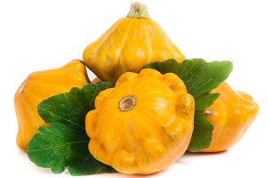 four yellow pattypan squash with leaf isolated on white background