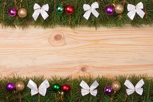 Christmas frame made of fir branches decorated with white bows and balls on a light wooden background