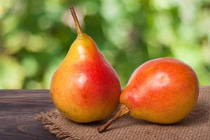 two pears on a dark wooden table with  blurred background