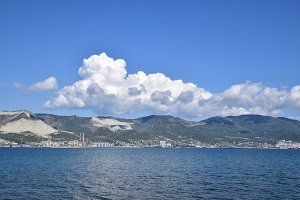 Sea bay landscape Tsemess. Mountains and clouds in the sky. In the distance can be seen the Marine cargo port