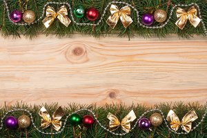 Christmas frame made of fir branches decorated with golden bows beads and balls on a light wooden background