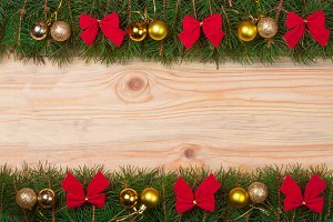 Christmas frame made of fir branches decorated with red bows and golden balls on a light wooden background
