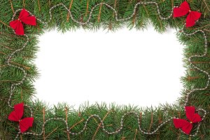 Christmas frame made of fir branches decorated with beads and red bows isolated on white background