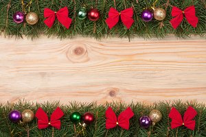 Christmas frame made of fir branches decorated with red bows and balls on a light wooden background