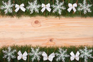 Christmas frame made of fir branches decorated with snowflakes and white bows on a light wooden background
