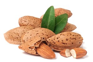 heap of almonds in their skins and peeled with leaf isolated on white background