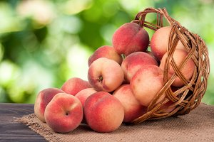 peaches in a wicker basket on wooden table with blurred background