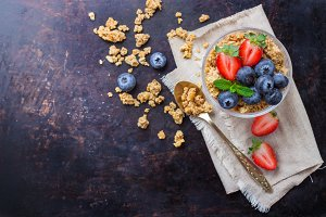 Homemade muesli granola in glass with berries on rusty table
