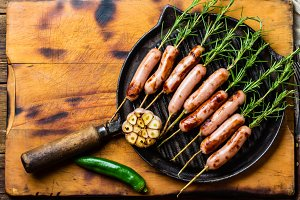 Grilled sausages on rosemary skewers, grill iron pan.
