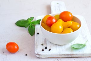 Bowl with yellow and red cherry tomatoes, copy space