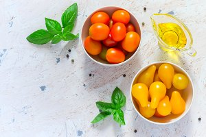 Red and yellow cherry tomatoes in bowls. Top view with copy spac