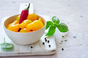 bowl of yellow cherry tomatoes and hot pepper, copy space