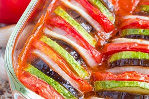 Homemade vegetable ratatouille in glass dish, cooked in oven, vertical