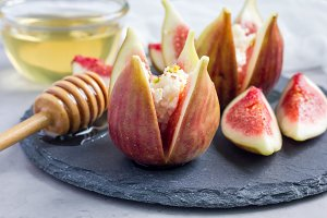 Figs, cheese, pistachio and honey dessert on slate plate, horizontal
