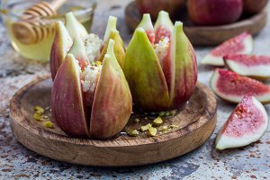 Figs, cheese, pistachio and honey dessert on wooden plate, horizontal