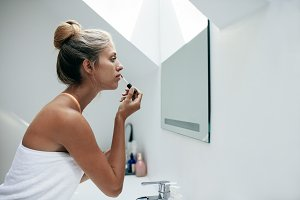 Woman applying lipstick in bathroom
