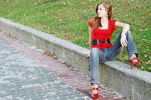 woman sit on a road kerb in park