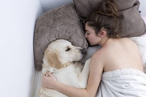 Teenage girl sleeping with her dog