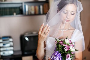 Pretty bride looks at a bouquet