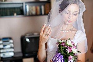 Pretty bride looks at a bouquet